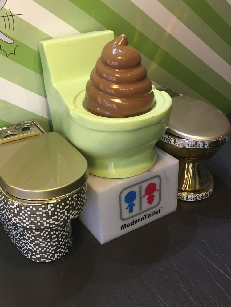 Toilets with golden lids and a urinal with a bunch of ice cream poo