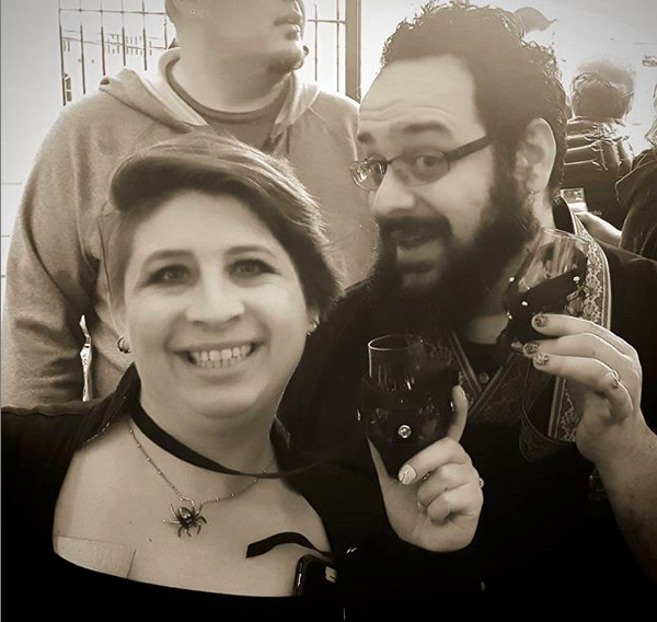 Two people in b/w photo holding up beer glasses