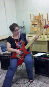 Woman with glasses poses with a red bass guitar
