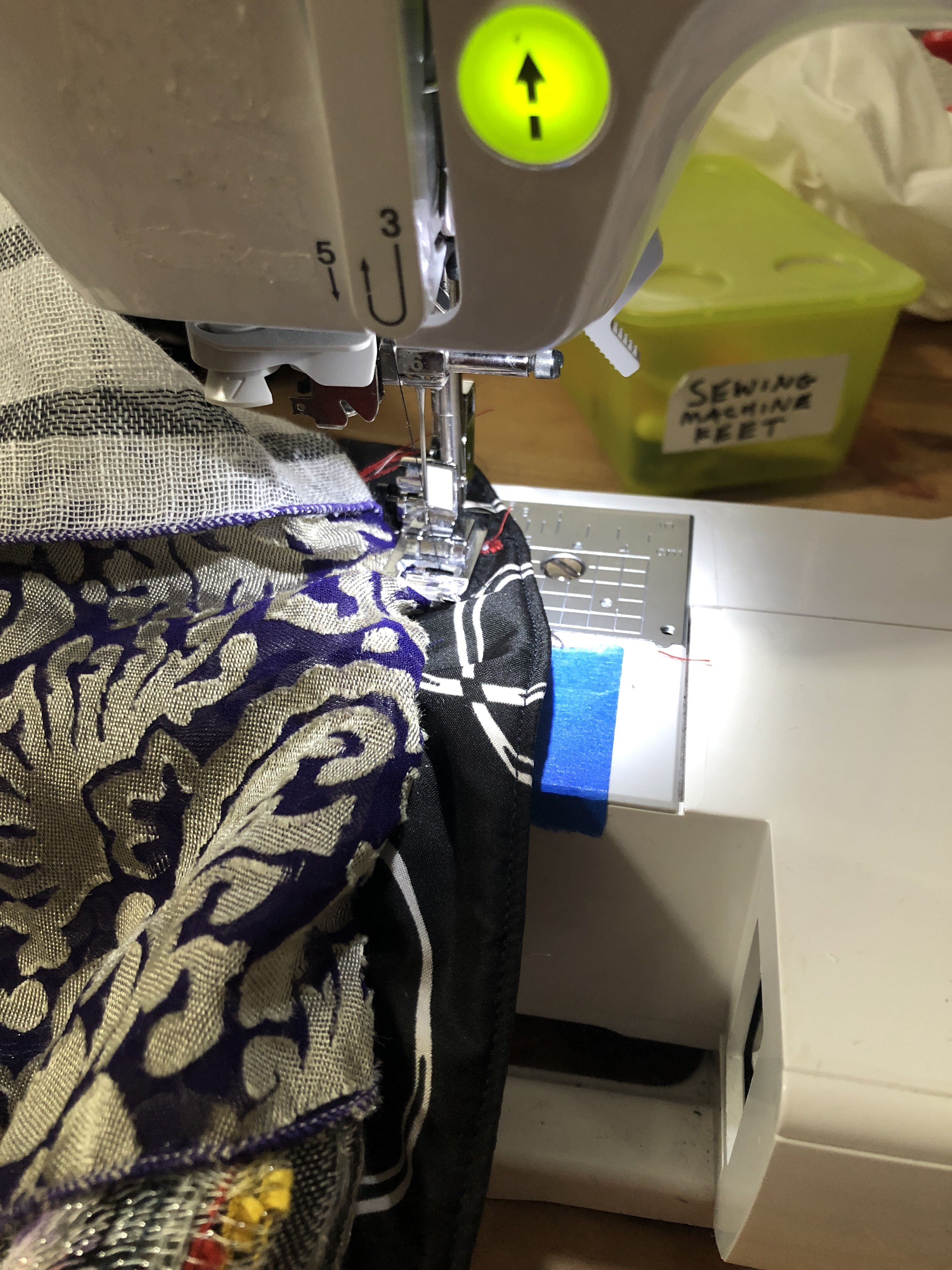 sewing machine close-up sewing purple and gold fabric